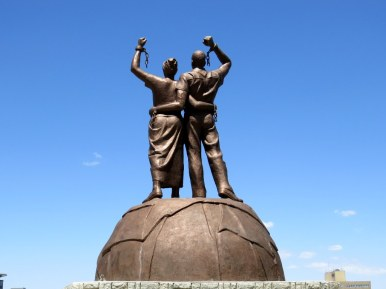 "Statue of a man and woman representing the struggle for independence with words from the Namibian National Anthem, ""Their blood waters our freedom"" written below."